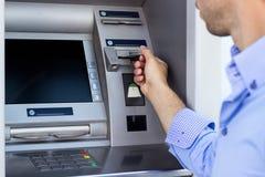 Man som använder en ATM Arkivbild