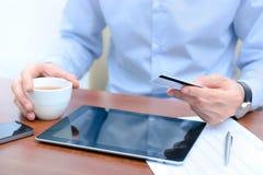 Man som använder en kreditkort för online-shopping Arkivfoto