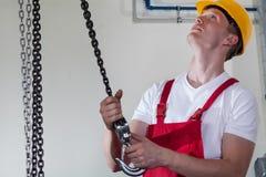 Man som använder lyftande kroken på arbete Arkivfoto