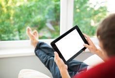 Man som använder minnestavlan på soffan Fotografering för Bildbyråer