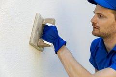 man som applicerar dekorativ fasadmurbruk med mursleven på husyttersida arkivfoto