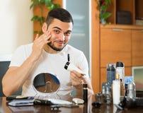 Man som applicerar kräm- hemmastatt för ansiktsbehandling Royaltyfri Foto