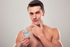Man som applicerar lotion efter rakning på framsida Royaltyfri Foto