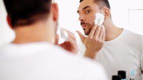 Man som applicerar raka skum till skägget på badrummet arkivfilmer