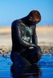 Man som applicerar svart som utomhus läker lera Arkivfoto