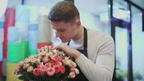 Man som arbetar som blomsterhandlare i blomsterhandel arkivfilmer