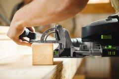 Man som arbetar med att snida utrustning i seminarium Elektronisk apparat Royaltyfri Bild