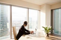 Man som arbetar på bärbara datorn med virtuell verklighetexponeringsglas Royaltyfria Foton