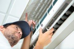 Man som arbetar på betingande enhet för luft Royaltyfri Fotografi