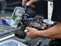 Man som arbetar på den radio kontrollerade barnvagnbilmodellen Arkivbilder