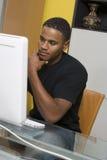 Man som arbetar på den skrivbords- datoren Arkivbild