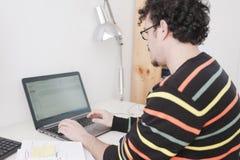 Man som arbetar på en hem- studio arkivbild
