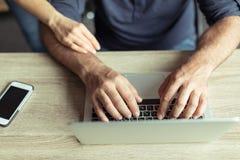 Man som arbetar på hemmastadd kontorsarbetsplats för bärbar dator Arkivfoton