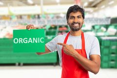 Man som arbetar på livsmedelsbutiken som framlägger organisk text på papper arkivbilder