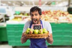 Man som arbetar på stormarknaden som annonserar försäljning på äpplen royaltyfria foton