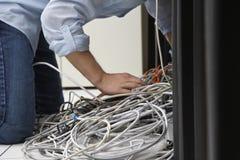 Man som arbetar på tilltrasslade datortrådar Fotografering för Bildbyråer