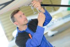 Man som arbetar på undersidaflygplan royaltyfria bilder