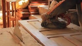 Man som arbetar sandpappra en ädelträdörr med en gammal bälteslipmaskin i hans hem- seminarium stock video