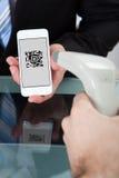 Man som avläser en köpkod på en mobil Arkivfoton
