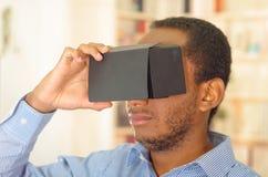 Man som bär den blåa skjortan som testar den vitrual verklighetmobila enheten, hållande exponeringsglas som är främsta av ögon Arkivbild