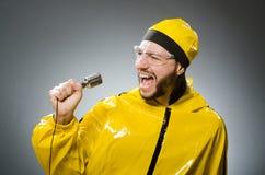 Man som bär den gula dräkten med mic Royaltyfri Bild