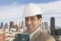 Man som bär den hårda hatten mot stads- stad Royaltyfri Bild