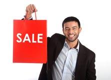 Man som bär en röd försäljningsshoppingpåse royaltyfri bild