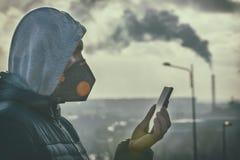 Man som bär en verklig anti--smog framsidamaskering och kontrollerar aktuell luftförorening med den smarta telefonappen royaltyfri bild