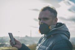 Man som bär en verklig anti--smog framsidamaskering och kontrollerar aktuell luftförorening med den smarta telefonappen royaltyfri foto