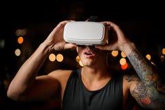 Man som bär exponeringsglas för VR-hörlurar med mikrofon som 3D delightfully ser upp med hans öppna mun Arkivfoto