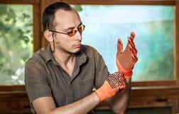 Man som bär skyddande handskar Arkivbild