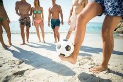 Man som balanserar fotbollbollen mot vänner Royaltyfria Foton