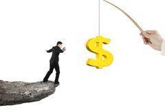 Man som balanserar guld- drag för fiske för dollartecken som isoleras på vit Arkivbild