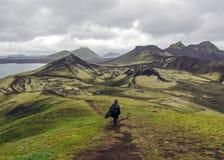 Man som bara fotvandrar in i det lösa beundra vulkaniska landskapet med den tunga ryggsäcken Begrepp för reslust för lopplivsstil arkivfoton
