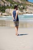 Man som bara går på den avskilda stranden med dagboken Arkivbild