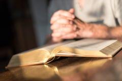 Man som ber händer på en bibel royaltyfria bilder