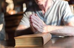 Man som ber händer på en bibel arkivfoto