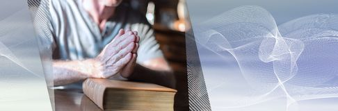 Man som ber händer på en bibel panorama- baner royaltyfri fotografi