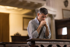 Man som ber i kyrkan royaltyfri bild