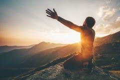 Man som ber på lyftta händer för solnedgång berg arkivbild