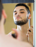 Man som besprutar doftdoft Fotografering för Bildbyråer