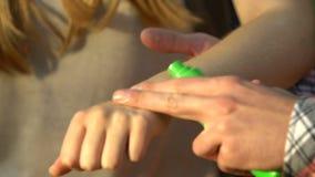 Man som besprutar myggaimpregneringsmedlet på den kvinnliga armen som trekking i skog, insekticid stock video