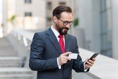 Man som betalar med kreditkorten på den smarta telefonen utanför Mogen affärsmandanandebeställning med kreditkorten en telefon, m royaltyfri bild