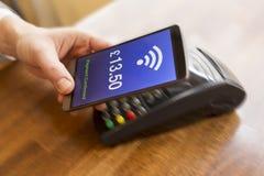 Man som betalar med NFC-teknologi på mobiltelefonen Pund engelsk ve Arkivfoto