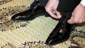 Man som binder skosnöre på svarta skor stock video