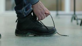 Man som binder skosnöret på kängorna arkivfilmer