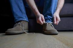Man som binder tillfälliga skor Arkivbilder