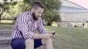 Man som bläddrar smartphonen som sitter på trappa arkivfilmer