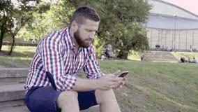 Man som bläddrar smartphonen som sitter på trappa Glidare- och pannaskott arkivfilmer