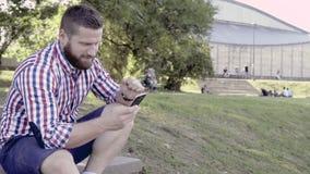Man som bläddrar smartphonen som sitter på trappa Glidareskott som lämnas stock video